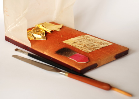 This picture shows gilding tools used for both water and oil gilding. The gold leaf is held and cut on a leather palette. A knife, similar to a painting knife, is used to cut the gold as necessary. Brushes are used to move the gold to the place to be gilded, and to press it into the mordant as necessary.